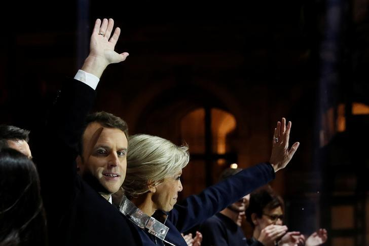 French President elect Emmanuel Macron celebrates on stage with his wife Brigitte Trogneux during his victory rally near the Louvre museum after results in the 2017 presidential election in Paris, France, May 7, 2017.    REUTERS/Thomas Samson/Pool