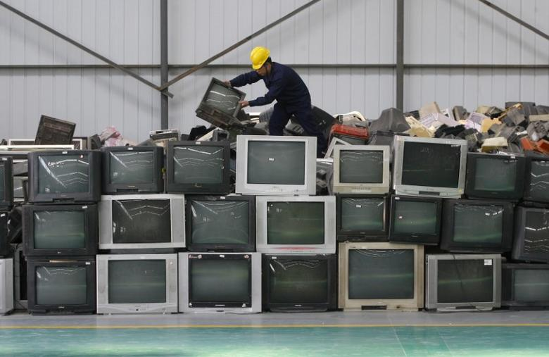 An employee arranges discarded televisions at a newly opened electronic waste recycling factory in Wuhan, Hubei province March 29, 2011. REUTERS/Stringer