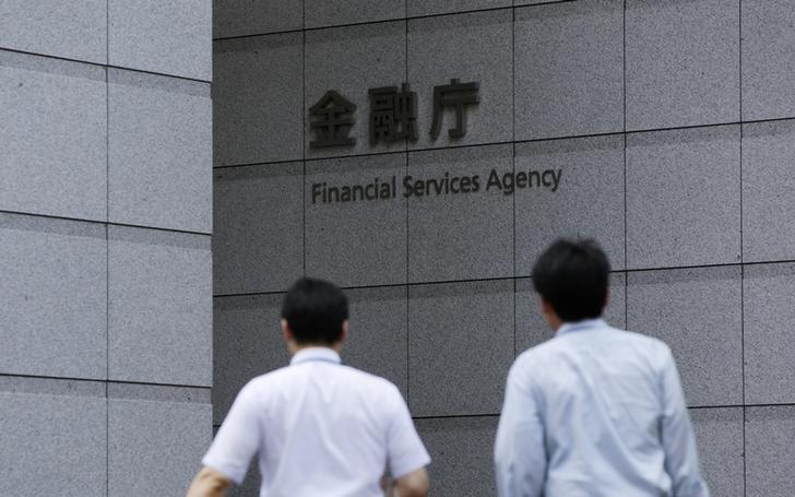 Men walk toward a sign of Japan's Financial Services Agency in Tokyo August 7, 2014.  REUTERS/Toru Hanai