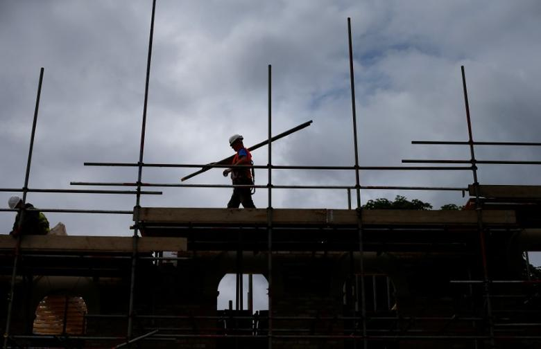 FILE PHOTO - A builder assembles scaffolding as he works on new homes being built for private sale on a council housing estate, in south London June 3, 2014.  REUTERS/Andrew Winning/File Photo