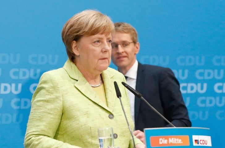 Daniel Guenther, top candidate of the Christian Democratic Union (CDU) and German Chancellor Angela Merkel address a news conference after the Schleswig-Holstein regional state elections, in Berlin, Germany, May 8, 2017. REUTERS/Fabrizio Bensch