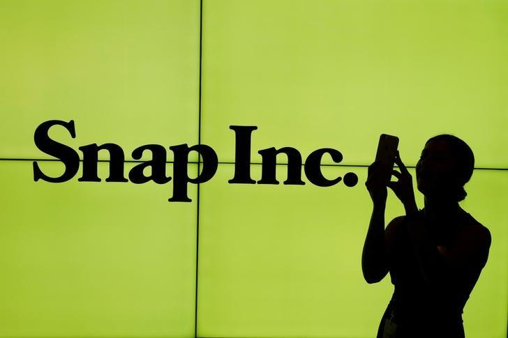 A woman stands in front of the logo of Snap Inc. on the floor of the New York Stock Exchange (NYSE) while waiting for Snap Inc. to post their IPO, in New York City, NY, U.S. March 2, 2017. REUTERS/Lucas Jackson/File Photo