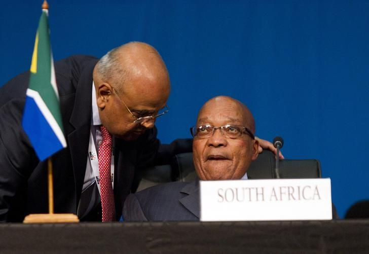 FILE PHOTO: South Africa's Finance Minister Pravin Gordhan speaks to President Jacob Zuma (R) during closing remarks during the 5th BRICS Summit in Durban, March 27, 2013. REUTERS/Rogan Ward/Files