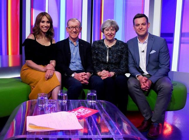 5月9日、英国のメイ首相夫妻がBBCテレビのインタビューに応じた。メイ首相は60歳、夫のフィリップさんは1歳年下で、投資家向け広報(IR)の仕事をしている。家事の分担やなれ初めについても語り、フィリップさんは質問に「一目ぼれだった」と答えた。写真は英保守党提供。BBC司会者2人(両端)と夫妻(2017年 ロイター)
