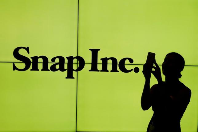 FILE PHOTO: A woman stands in front of the logo of Snap Inc. on the floor of the New York Stock Exchange (NYSE) while waiting for Snap Inc. to post their IPO, in New York City, NY, U.S. on March 2, 2017. REUTERS/Lucas Jackson/File Photo