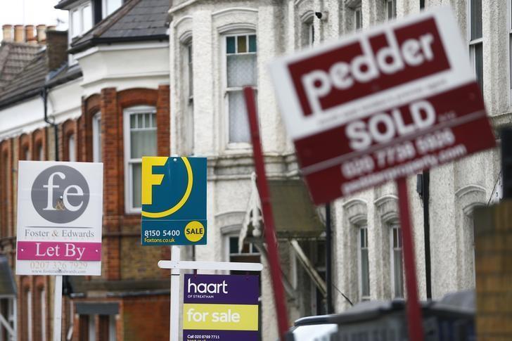 资料图片:伦敦南部街区房屋外的房地产中介广告。REUTERS/Andrew Winning