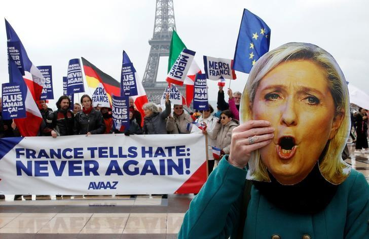 A person holds a mask of France's National Front (FN) defeated presidential candidate, Marine Le Pen, as people gather with French and European flags near the Eiffel Tower and a banner with the message, ''France tells Hate: Never Again'' the day after presidential elections in the country, in Paris, France, May 8, 2017.  REUTER/Pascal Rossignol/Files