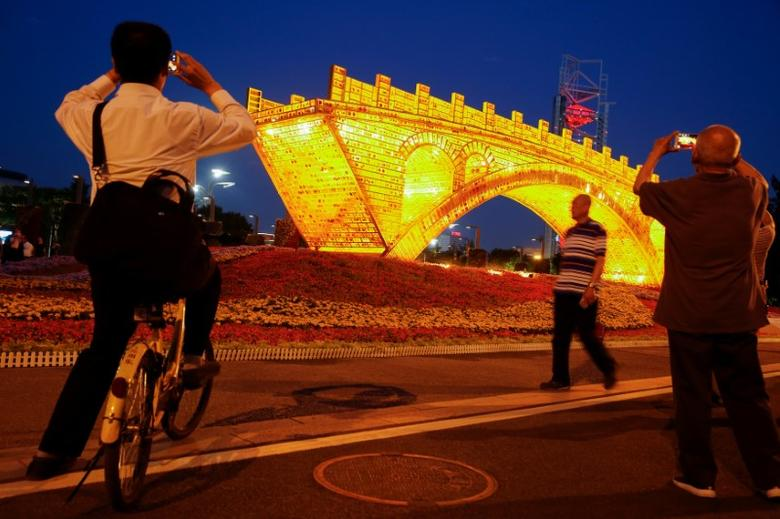 People take pictures of the ''Golden Bridge on Silk Road'' installation by artist Shu Yong, set up ahead of the Belt and Road Forum in Beijing, China May 10, 2017. REUTERS/Thomas Peter
