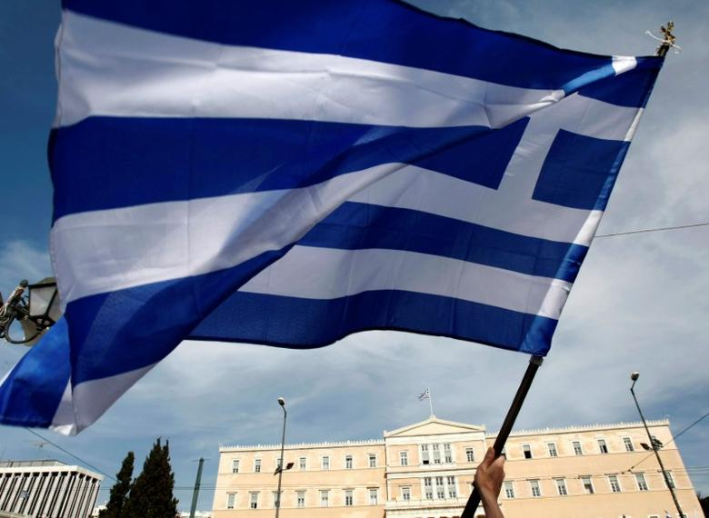 FILE PHOTO: A woman waves a Greek flag in front of parliament during a protest against the government's austerity measures in Athens May 3, 2010.  REUTERS/John Kolesidis/File photo