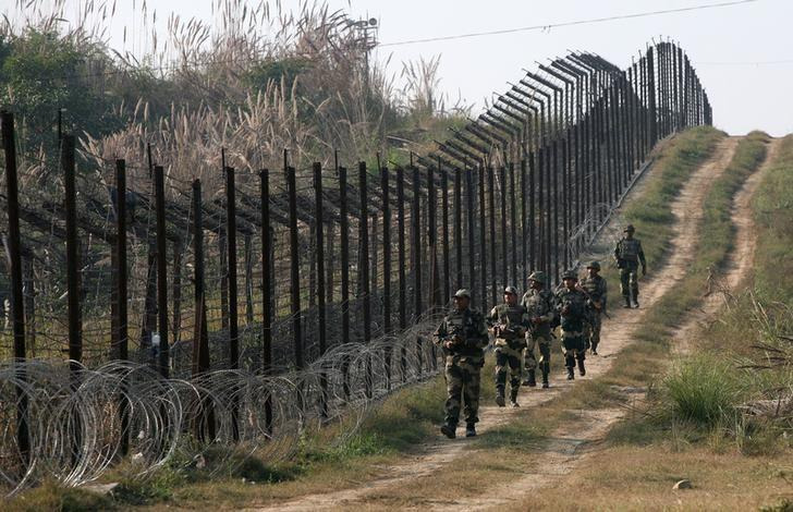 Indian Border Security Force (BSF) soldiers patrol the fenced border with Pakistan at Babiya village in Hira Nagar sector, about 80 km (50 miles) from Jammu December 6, 2013. REUTERS/Mukesh Gupta/Files