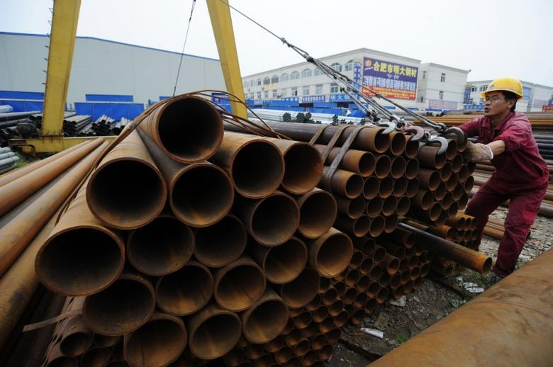 A worker transports seamless steel pipes at a steel market in Hefei, Anhui province, October 8, 2009. REUTERS/Stringer