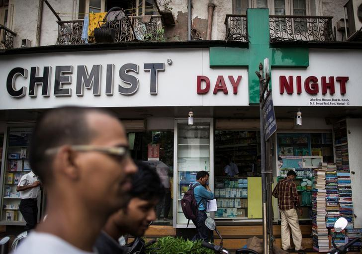 FILE PHOTO: People walk past a chemist shop at a market in Mumbai, India, June 24, 2014. REUTERS/Danish Siddiqui/File photo