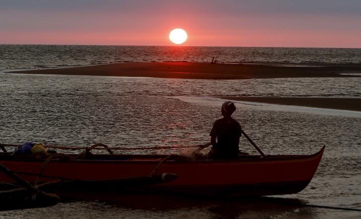 资料图片:2015年4月,南海,一名渔民在欣赏海上日落景象。REUTERS/Erik De Castro