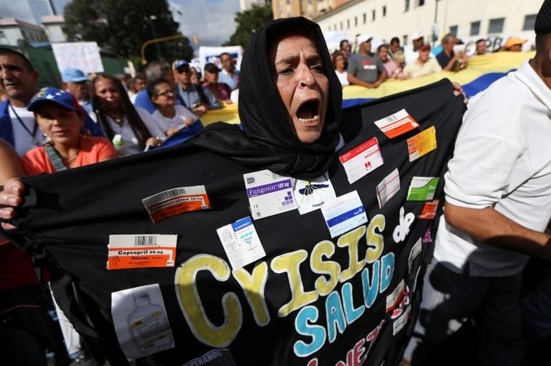 FILE PHOTO: A woman wearing a costume with medicine boxes that reads ''Health crisis'' shouts slogans during a rally of workers of the health sector due to the shortages of basic medical supplies and against Venezuelan President Nicolas Maduro's government in Caracas, Venezuela February 7, 2017. REUTERS/Carlos Garcia Rawlins