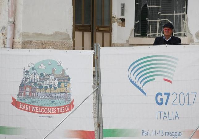 A man looks on behind a barrier in front of the Norman Swabian Castle, where Finance leaders of the G7 advanced economies will hold three days of talks, in the southern Italian city of Bari, Italy May 11, 2017. REUTERS/Alessandro Bianchi