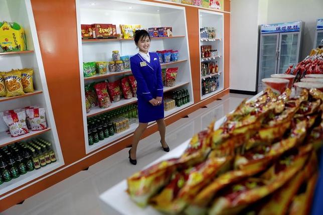 5月8日、北朝鮮への追加制裁が迫るなか、同国を訪れた人たちの大半は、中国からの輸入品に取って代わる「メイド・イン・北朝鮮」製品を、以前より多く目にすると語る。写真は首都平壌にある食料品店の店員。4月撮影(2017年 ロイター/Damir Sagolj)