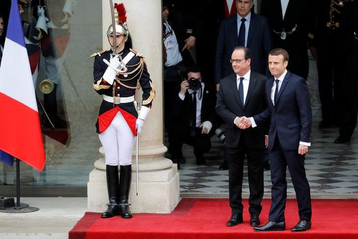 Outgoing French President Francois Hollande (L) greets President-elect Emmanuel Macron who arrives to attend the handover ceremony at the Elysee Palace in Paris, France, May 14, 2017.   REUTERS/Patrick Kovarik/Pool