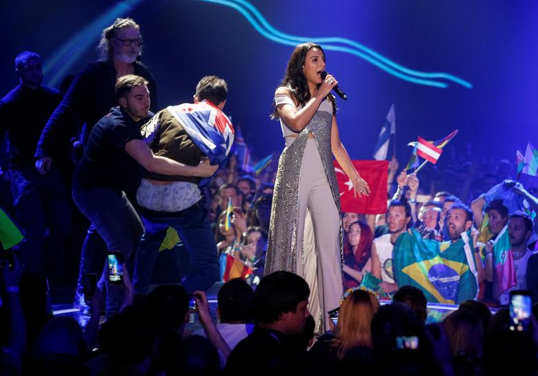 Ukraine's Jamala performs a song as security detain a fan. REUTERS/Stringer