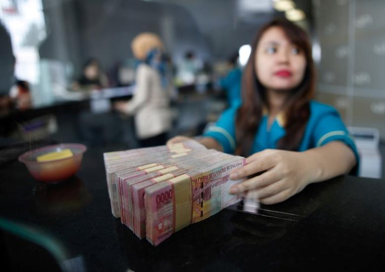 A teller at a money changer handles Indonesia rupiah bank notes in Jakarta, Indonesia November 11, 2016. REUTERS/Darren Whiteside/File Photo