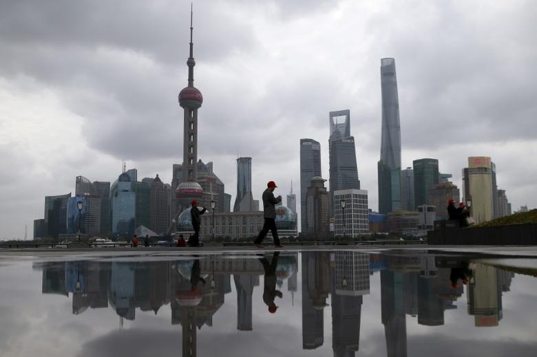 资料图片:2016年3月,上海,浦东陆家嘴金融区及对面的外滩区域的行人。REUTERS/Aly Song