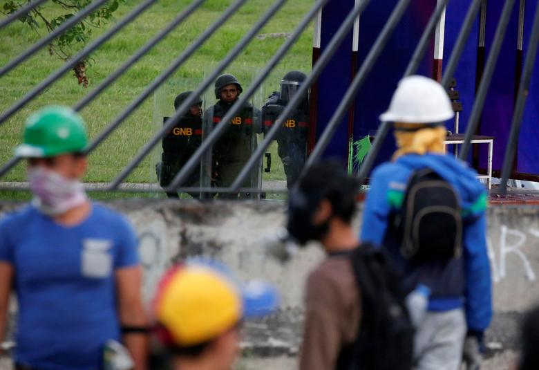 Riot security forces look on as opposition supporters block an avenue while rallying against President Nicolas Maduro in Caracas, Venezuela, May 15, 2017. REUTERS/Carlos Garcia Rawlins