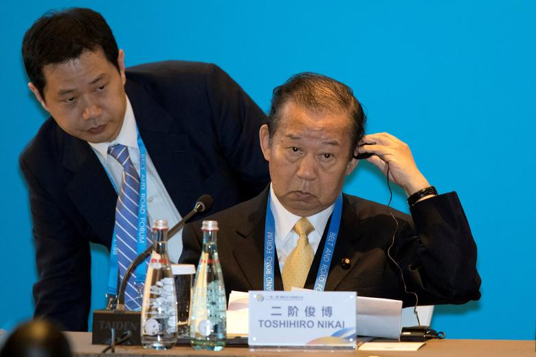 Toshihiro Nikai, Secretary General of the Japanese Liberal Democratic Party adjusts his ear piece before a session on connectivity of development policies and strategies held as part of the Belt and Road Forum in Beijing, China, May 14, 2017. REUTERS/Ng Han Guan/Pool