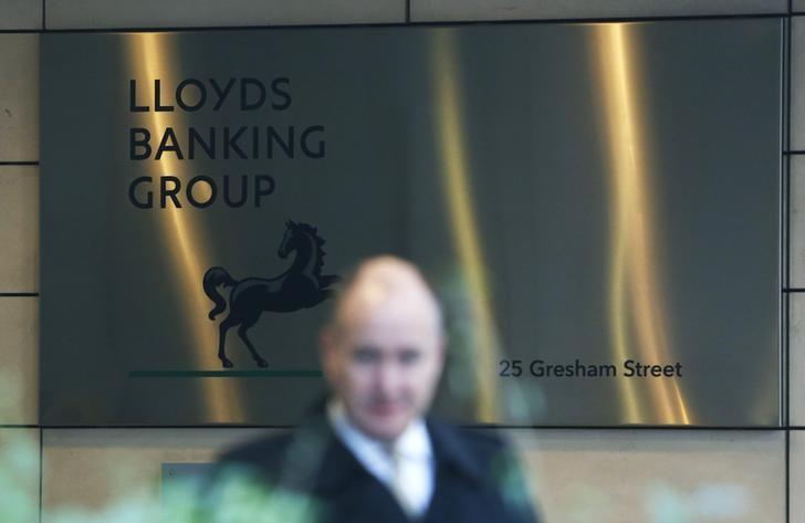 FILE PHOTO: A man walks past the entrance to the head office of Lloyds Banking Group in the City of London December 11, 2013. REUTERS/Olivia Harris