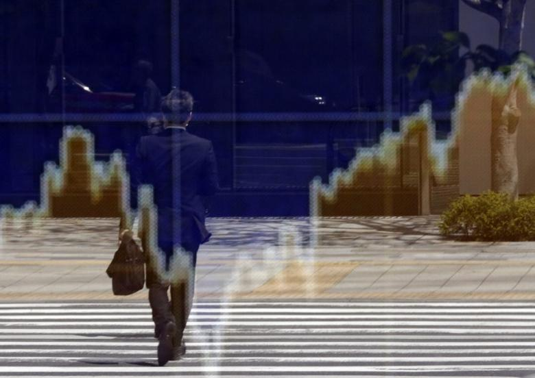 A man is reflected in an electronic board outside a brokerage in Tokyo April 22, 2013. REUTERS/Toru Hanai