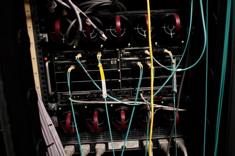 FILE PHOTO: Cables and computers are seen inside a data centre at an office in the heart of the financial district in London, Britain May 15, 2017. REUTERS/Dylan Martinez
