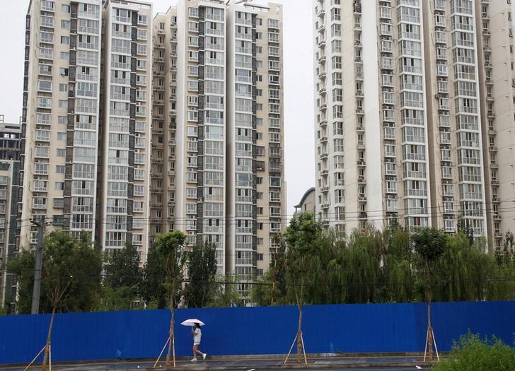 资料图片:2016年7月,北京,一名女子路过一处住宅区。REUTERS/Thomas Peter