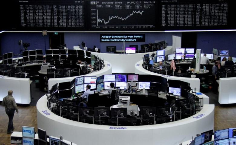 FILE PHOTO: Traders work in front of the German share price index, DAX board, at the stock exchange in Frankfurt, Germany, May 10, 2017. REUTERS/Staff/File Photo