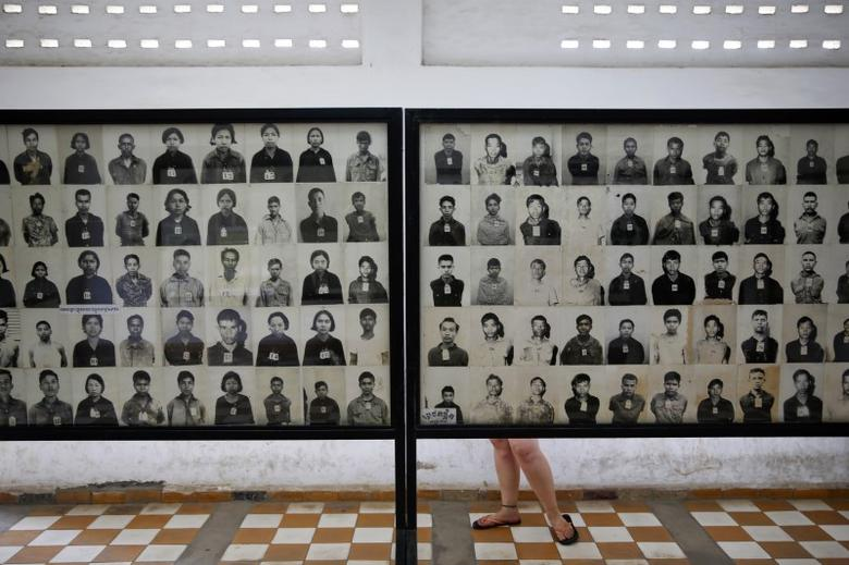 A visitor looks at pictures of victims of Khmer Rouge regime at the former notorious Tuol Sleng prison that is now the Genocide Museum, in Phnom Penh August 5, 2014.  REUTERS/Damir Sagolj
