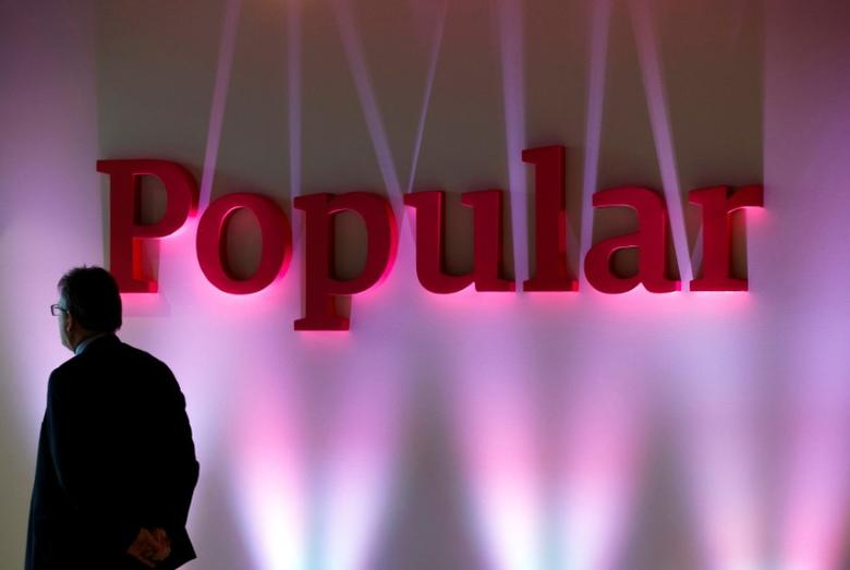 FILE PHOTO: A man stands next to the logo of Spain's Banco Popular during the bank's results presentation in Madrid January 30, 2015. REUTERS/Sergio Perez/File Photo