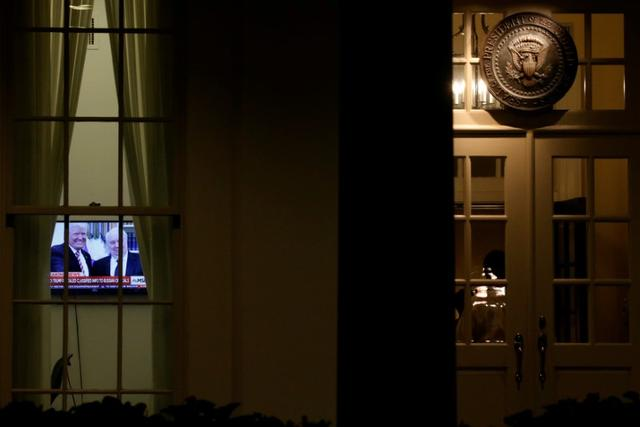 FILE PHOTO A television plays a news report on U.S. President Donald Trump's recent Oval Office meeting with Russia's Ambassador to the U.S. Sergei Kislyak as night falls on offices and the entrance of the West Wing of the White House in Washington, U.S. May 15, 2017.  REUTERS/Jonathan Ernst/File Photo