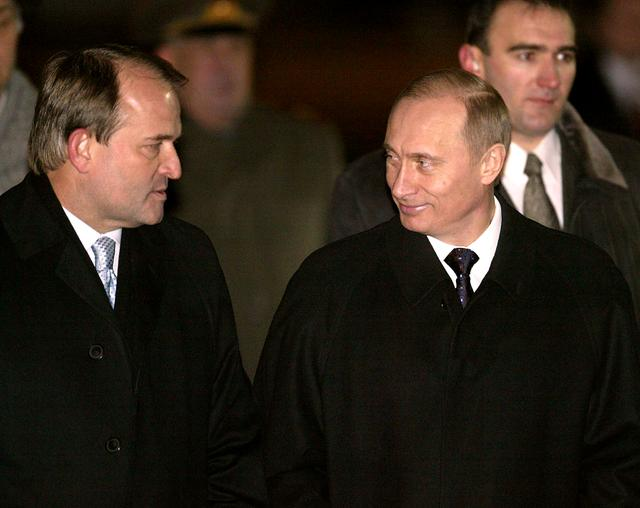 FILE PHOTO Russian President Vladimir Putin (R) smiles at Ukrainian President's administration head Viktor Medvedchuk as Putin arrives in Kiev, January 27, 2003.  REUTERS/Alexander Natruskin/File Photo
