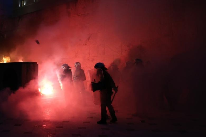 Riot police stand among flare smoke on the Tomb of the Unknown Soldier burns during clashes outside the parliament building as Greek lawmakers vote on the latest round of austerity Greece has agreed with its lenders, in Athens, Greece, May 18, 2017.