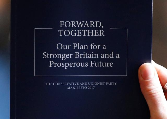 A woman holds up a copy of Britain's Prime Minister Theresa May's election manifesto at its launch in Halifax, May 18, 2017. REUTERS/Phil Noble