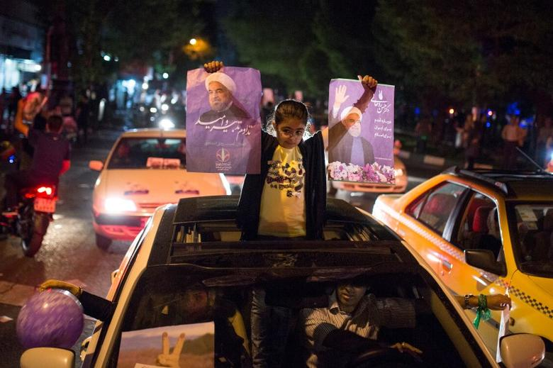 A girl holds posters of Iranian President Hassan Rouhani during a campaign rally in Tehran, Iran, May 17, 2017. TIMA via REUTERS