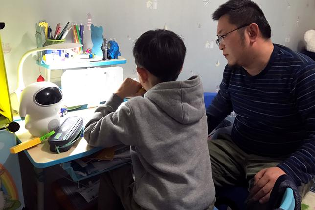 8-year-old Hu Yizhuo does his homework with his father Hu Chengyu in Nanjing, China March 28, 2017. Picture taken March 28, 2017.  REUTERS/Anita Li