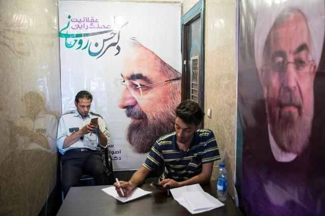 Men use their smartphones to follow election news as posters of Iran's President Hassan Rouhani are seen in Tehran, Iran May 17, 2017. REUTERS/TIMA