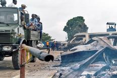 Security personnel sitting on a truck watch burned vehicles at the front gate of the Makala prison after it was attacked by supporters of jailed Christian sect leader Ne Muanda Nsemi in Kinshasa, Democratic Republic of the Congo May 17, 2017. REUTERS/Robert Carrubba