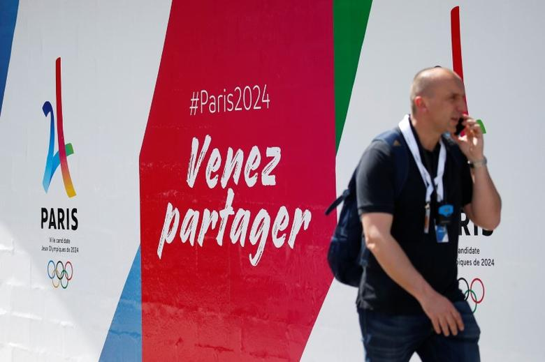 A journalist passes by the logo of the Paris candidacy for the 2024 Olympic and Paralympic Games at the Stade Jean Bouin during the press tour of the International Olympic Committee Evaluation Commission, in Paris, May 15, 2017.  REUTERS/Gonzalo Fuentes