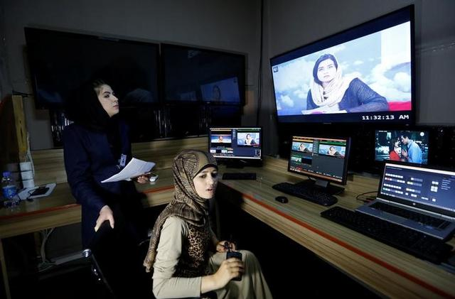 Khatira Ahmadi (R), 20, producer of Zan TV (women's TV) station, works in the editing room in Kabul, Afghanistan May 8, 2017. REUTERS/Mohammad Ismail