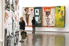 Visitantes observan las telas del artista, Jean-Michel Basquiat, en el Museo de Arte Moderno en París, Francia.14/10/2010. Una pintura poco vista de Jean-Michel Basquiat que se vendió en 1984 por 19.000 dólares alcanzó la increíble cifra de 110,5 millones de dólares en una subasta de Sotheby's, el segundo precio más alto pagado jamás por una obra de arte contemporáneo.  REUTERS/Benoit Tessier