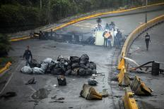 Local residents cross a barricade following days of protest against Venezuelan President Nicolas Maduro in the city of Los Teques, near Caracas, Venezuela, May 19, 2017. REUTERS/Carlos Barria