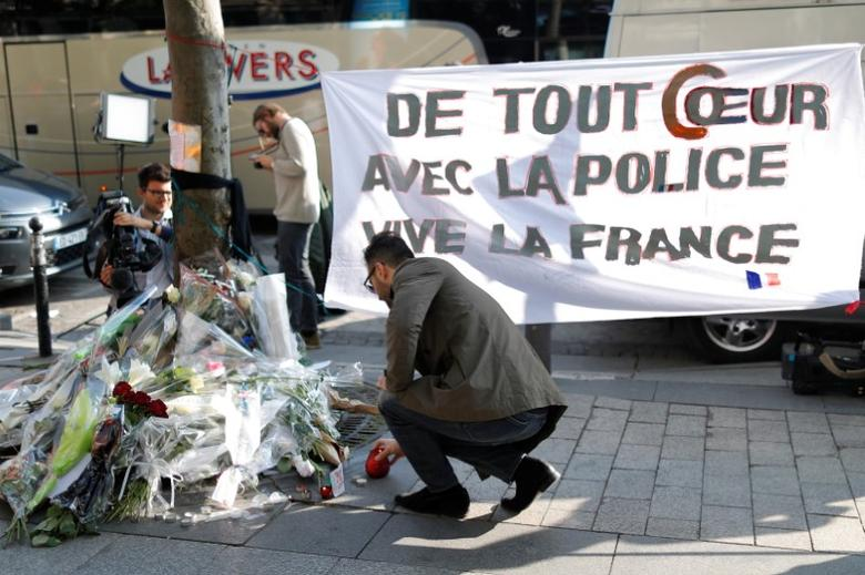 A man lights on a candle on the Champs Elysees Avenue the day after a policeman was killed and two others were wounded in a shooting incident in Paris, France, April 21, 2017. The banner reads ''With all my heart with the police, Long live France''.  REUTERS/Charles Platiau