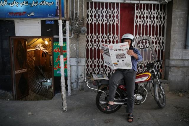 A man reads a newspaper, the day after the presidential election, in Tehran, Iran, May 20, 2017. TIMA via REUTERS