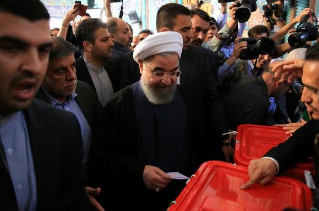 5月20日、イラン大統領選で、現職のロウハニ大統領(中央)が57%以上の票を獲得して再選を果たした。写真は19日、テヘランの投票所で撮影。提供写真(2017年 ロイター/TIMA)