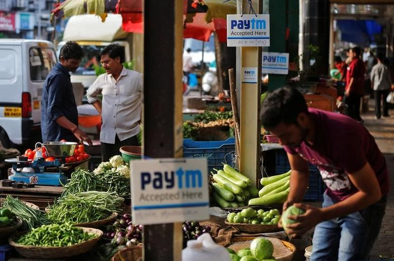 Advertisement boards of Paytm, a digital wallet company, are seen placed at stalls of roadside vegetable vendors as they wait for customers in Mumbai, November 19, 2016. REUTERS/Shailesh Andrade/Files