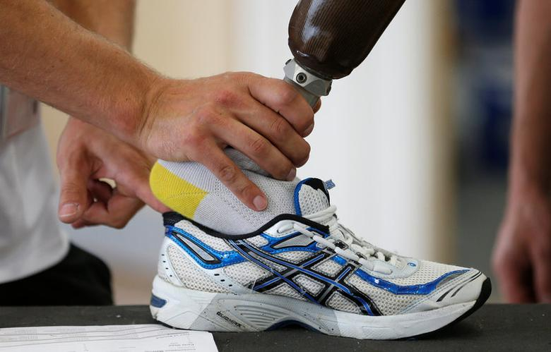 FILE PHOTO: A technician fits a prosthetic foot into a trainer in the Ottobock workshop at the Athlete's Village in the Olympic Park in Stratford, east London August 28, 2012. REUTERS/Suzanne Plunkett/File Photo